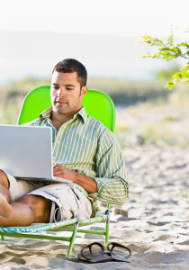 bigstock-man-using-laptop-at-beach-27199109
